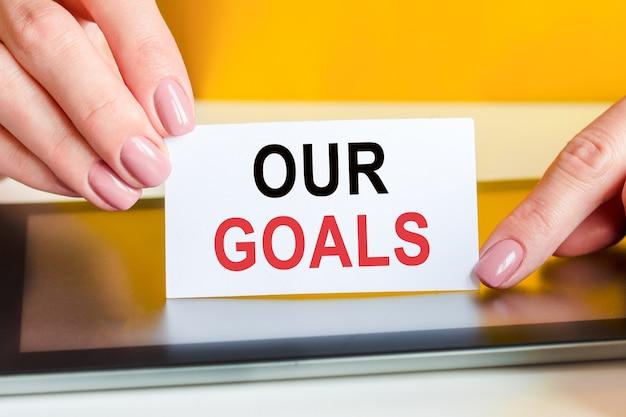 美しい女性の手には、私たちの目標というテキストが書かれた白い紙があります。ビジネス、マーケティング、財務の概念に使用できます。