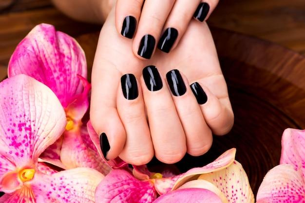 Mani di belle donne con manicure nera dopo procedure spa - concetto di trattamento spa