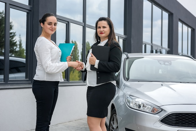 Красивые женщины пожимают руки возле новой машины, стоящей снаружи и улыбаются