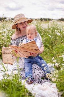 Beautiful women and her son sitting and reading book. high quality photo