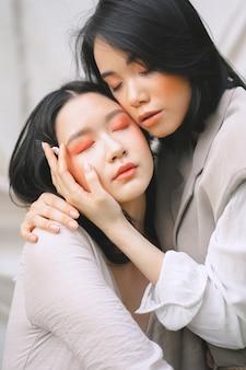 Красивые женщины, держа друг друга с закрытыми глазами в дневное время.