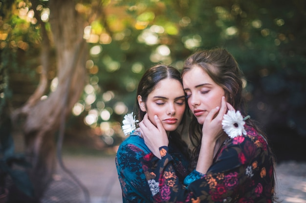Beautiful women holding flowers and hugging with closed eyes