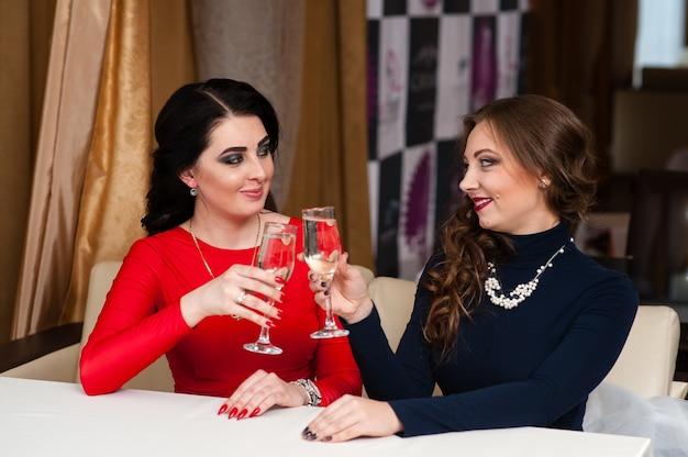Красивые женщины держат бокалы шампанского, делая тост