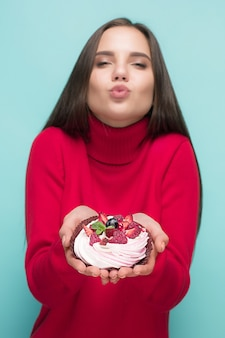 작은 케이크를 들고 아름 다운 여자입니다. 생일, 휴일, 다이어트. 파란색 배경 위에 스튜디오 초상화