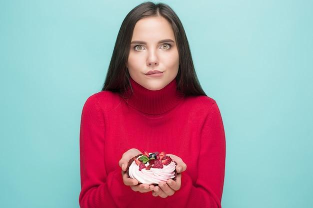 小さなケーキを持っている美しい女性。誕生日、休日。青い背景の上のスタジオの肖像画