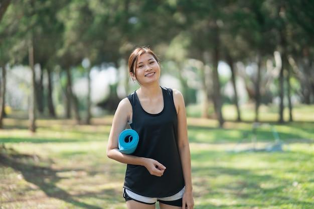 요가 매트를 들고 아름다운 여성이 정원에서 요가 운동을 준비합니다.