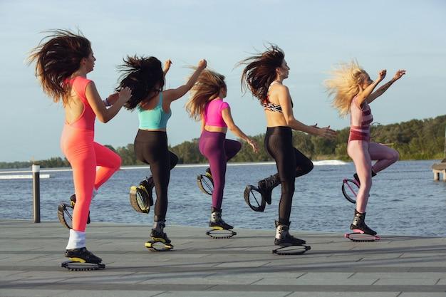 晴れた日には、カンゴーでジャンプするスポーツウェアの美しい女性が通りで靴をジャンプします。
