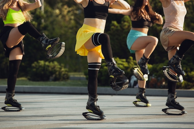 夏の晴れた日に、カンゴーでジャンプするスポーツウェアの美しい女性が通りで靴をジャンプします。高くジャンプする、アクティブな動き、アクション、フィットネス、ウェルネス。トレーニング中に女性モデルをフィットさせます。