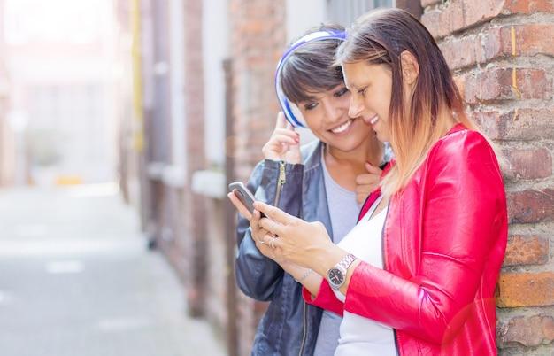 美しい女性が市内のスマートフォンと情報を共有しています