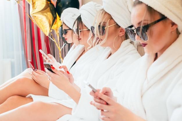 美しい女性のライフスタイル。自己保証が直面しています。手にスマートフォン。サングラス、バスローブ、ターバン