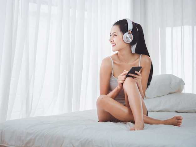 Beautiful women listening to music through the phone in bed