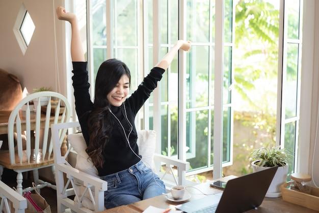 카페에서 음악을 듣고 노트북으로 일하는 아름다운 여성
