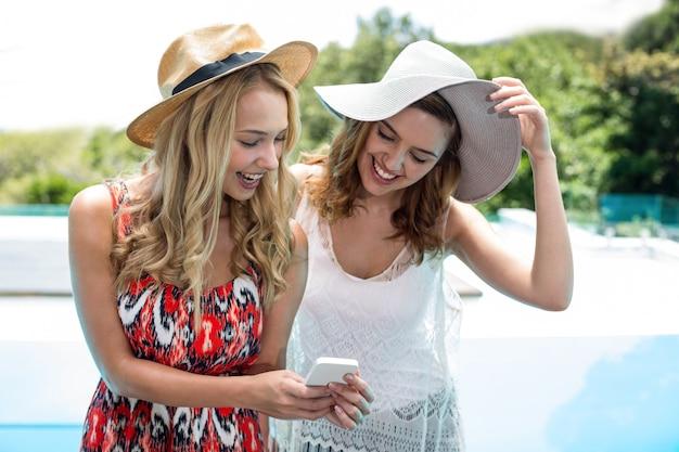 Красивые женщины смотрят на мобильный телефон и улыбаются