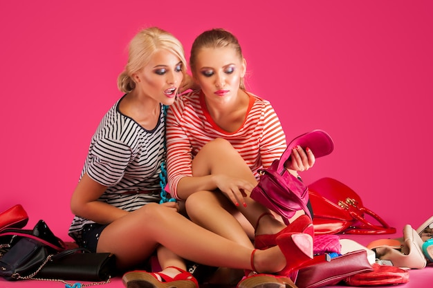 분홍색 벽에 아름 다운 여자입니다. 화려한 지갑과 가방과 신발로 둘러싸인 여성.