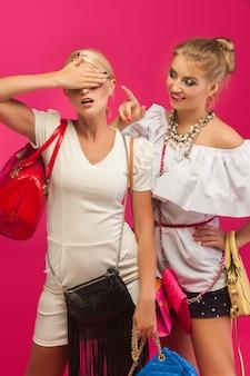 ピンクの壁の美しい女性。カラフルな財布とバッグと靴に囲まれた女性。