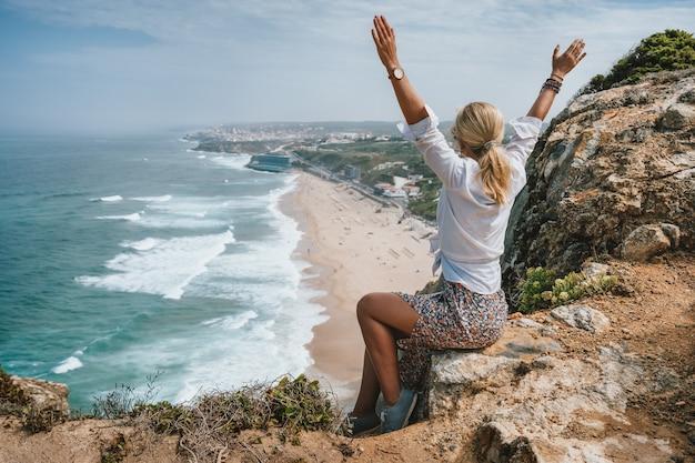 Praia da adraga, sintra, portugal에서 대서양 해안을 즐기는 손을 올리는 아름다운 여성