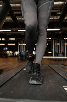 Beautiful women's athletic legs in black sportswear with black sneakers running on the treadmill at the gym