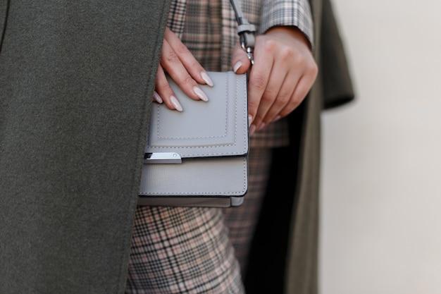 아름다운 여성의 세련된 회색 핸드백. 핸드백과 유행 코트에서 세련 된 젊은 여자. 확대