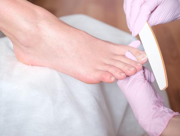 ビューティーサロスパマニキュアのペディキュアと美しい女性の足。ビューティーサロンのクローズアップでペディキュアの手順の過程で女性の足。足病医。足と爪の治療