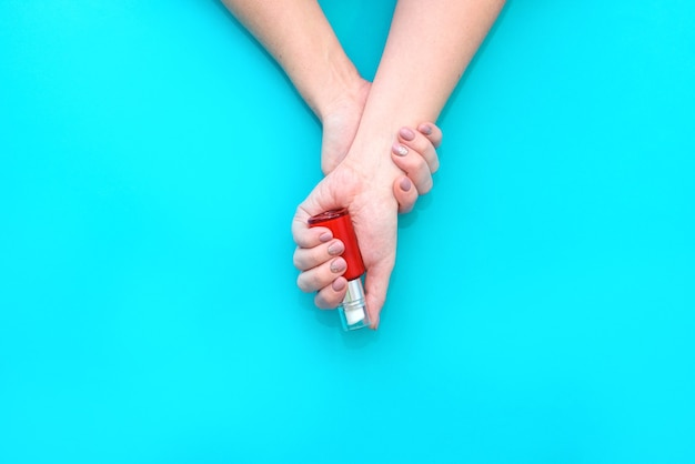 Красивые женские руки с нежным маникюром держат флакончик крема. плоская планировка.