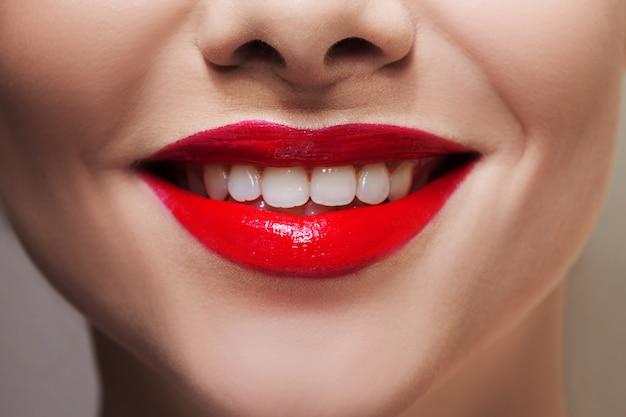 真っ赤な口紅と白い歯の美しい女性の唇。