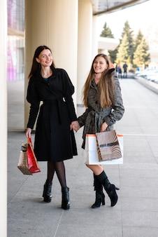 Красивые женщины делают покупки в торговом центре