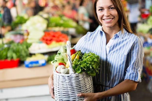 Красивые женщины делают покупки овощей и фруктов в супермаркете