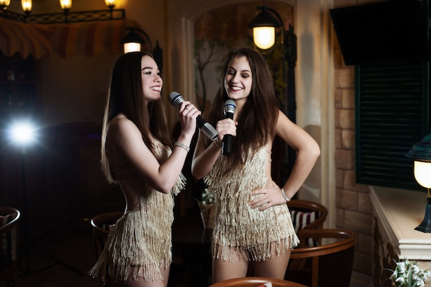 Beautiful women singing karaoke songs in microphones in restaurant