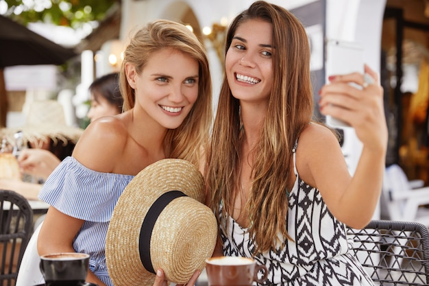 Beautiful women sit close to each other, pose for selfie against cafe interior, drink hot beverage, have happy expressions. two female friends make photo of themselves via modern smart phone