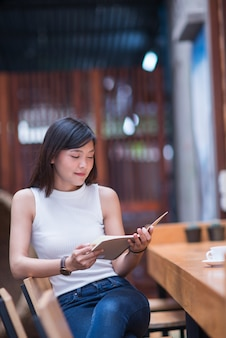 Beautiful women sitting by wooden table and reading book