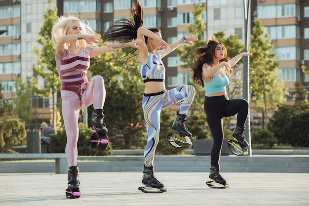 Beautiful women in sportswear jumping in a kangoo jumps shoes at the street on summer's sunny day
