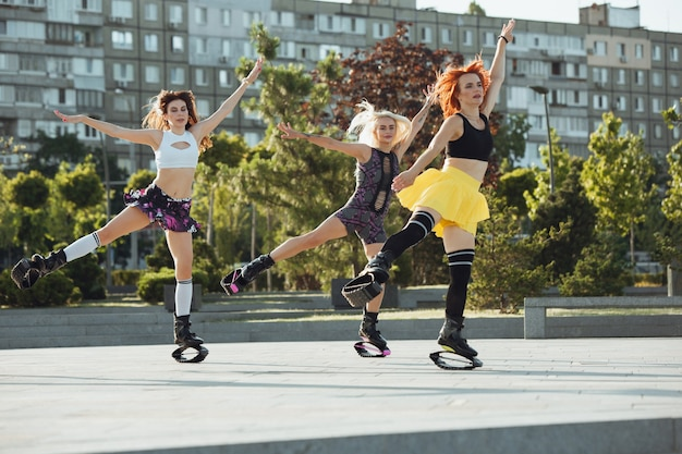 Beautiful women in sportswear jumping in a kangoo jumps shoes at the street