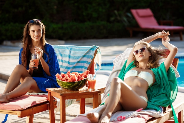 Beautiful women sunbathing, relaxing, resting on chaises near swimming pool