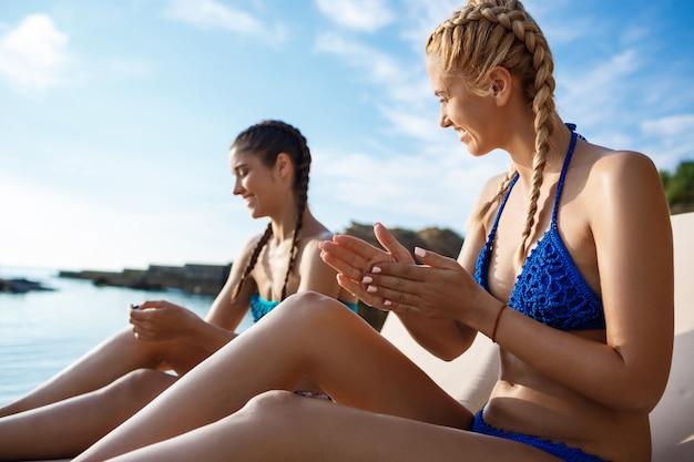 Belle donne in costume da bagno che sorridono, applicando la crema solare in riva al mare