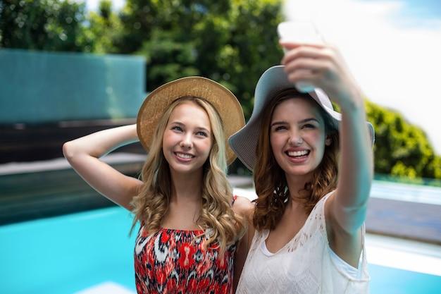 Красивые женщины, делающие селфи у бассейна