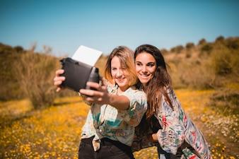 Beautiful women taking selfie in field