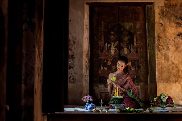 Девушка красивых женщин тайская держа лотос руки в традиционном тайском костюме с ayutthaya виска, культурой идентичности таиланда.
