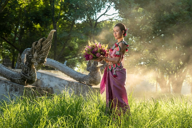 Beautiful women thai girl holding hand lotus in traditional thai costume with temple ayutthaya, identity culture of thailand .