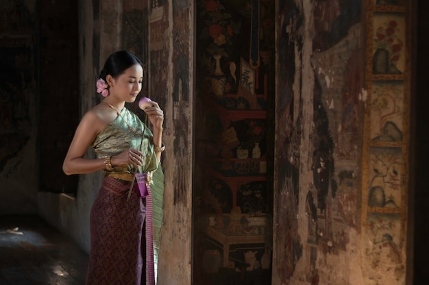 Beautiful women thai girl holding hand lotus in traditional thai costume with temple ayutthaya