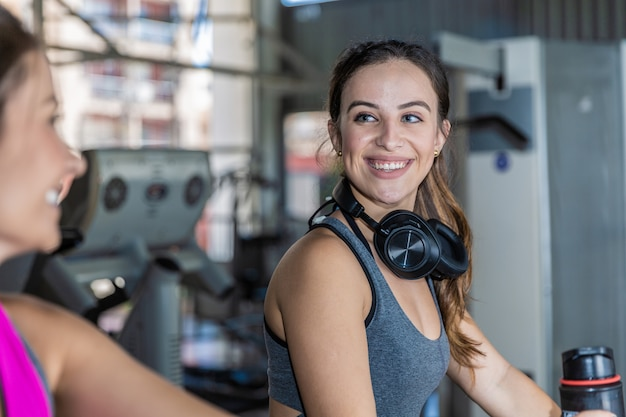 Beautiful women training in a gym. beautiful group of young women friends exercising on a treadmill at the bright modern gym.