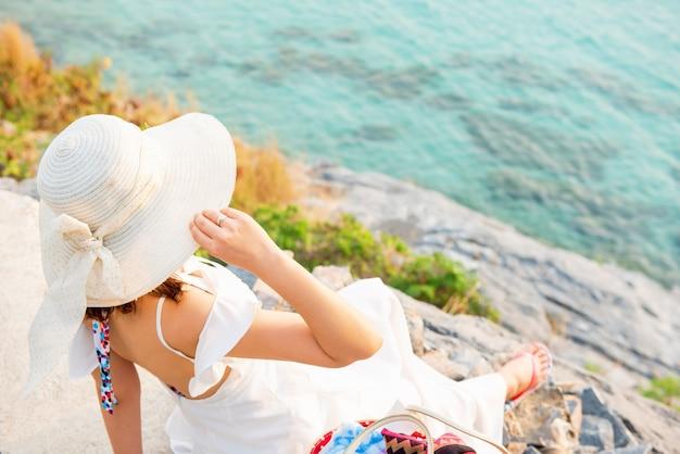 Красивые женщины путешествуют одни на пляже летом. море и небо на закате