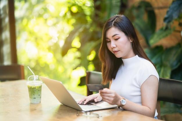 オンラインで買い物をするためにクレジットカードとラップトップを使用している美しい女性
