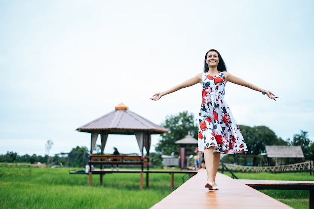 美しい女性は木製の橋の上を楽しく歩きます