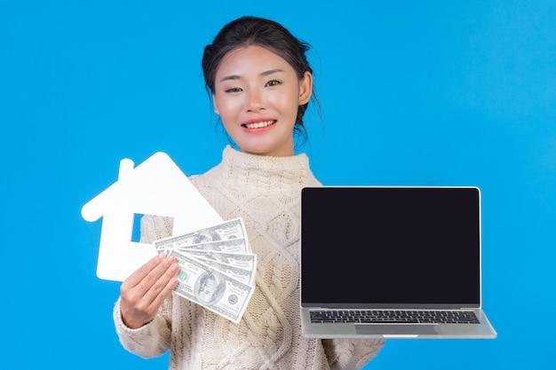 Красивые женщины, носить новый с длинными рукавами белый ковер, держа ноутбук. дом и доллар банкноты символы на синем. торговая