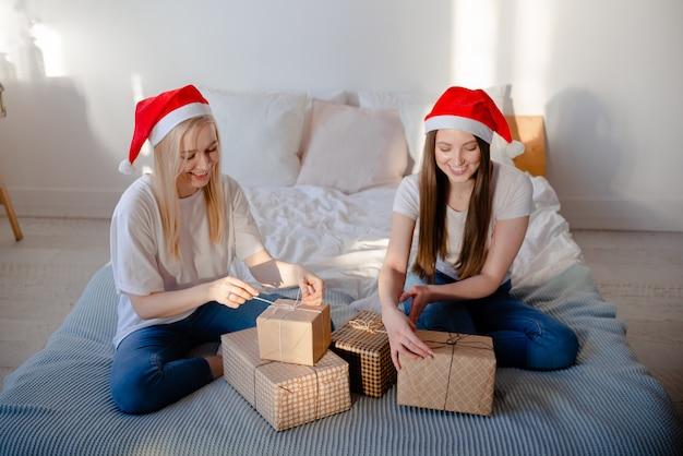 Beautiful women wearing santa hat girl making funny selfies. horizontal view copyspace holiday and beauty concept