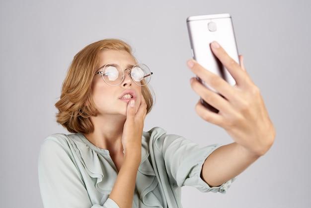 Красивые женщины с мобильным телефоном в руках фотографируются в рубашке