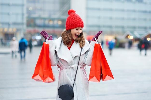 겨울 쇼핑 동안 가방을 가진 아름다운 여성
