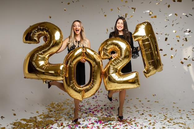 Belle donne con palloncini di capodanno 2021.