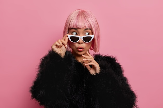 Beautiful wondered millennial girl wears pink hair wig, sunglasses and black fluffy sweater, scared to see something surprising and thrilling aside stands indoor over rosy wall. people, style, fashion