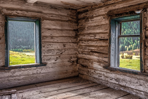 Beautiful wooden abandoned log house on mountains background
